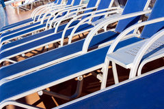 Sun loungers. Blue sunbeds on the deck of a cruise liner royalty free stock image