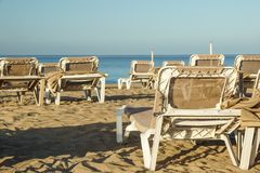 Sun loungers and closed umbrellas at a seaside resort , the calm and relaxed atmosphere of the summer holiday at sunset.  stock image