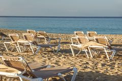 Sun loungers and closed umbrellas at a seaside resort , the calm and relaxed atmosphere of the summer holiday at sunset.  stock images