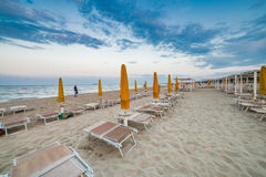 Sun loungers and umbrellas at seaside resort. Sun loungers and closed umbrellas at a seaside resort of Emilia Romagna on the Adriatic Riviera in Italy, the calm stock photos