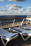 Sun loungers on cruise ship. Close up of striped sun loungers on deck of cruises ship, sea and cloudscape in background Stock Photography