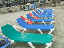 Sun loungers. Deck chairs on a beach. Sun loungers or deckchairs on a beach in Summer season Stock Photos
