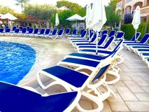 Sun loungers. Empty sun loungers by the pool blue Stock Image