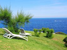 Sun loungers on a green with the background of the sea. Spain royalty free stock photography