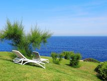 Sun loungers on a green with the background of the sea. Spain stock photo