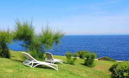 Sun loungers on a green with the background of the sea. Spain royalty free stock images