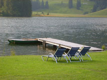 Sun loungers by lake. Three sun loungers by side of lake with small pier in summer scene stock photos