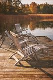 Sun loungers by lake. Lakeside wooden sun loungers in autumn setting stock photography