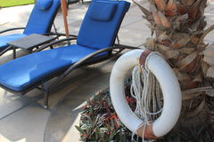 Sun loungers and life ring at a luxury resort Royalty Free Stock Photo