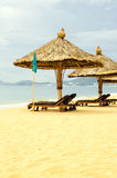 Sun loungers with parasols on a beach Royalty Free Stock Photography