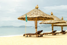 Sun loungers with parasols on a beach Royalty Free Stock Photo