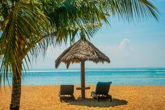 Sun loungers and parasols on the beach. Bali, Indonesia, Tanjung Benoa. Nusa Dua. Benoa sand beach view. Bali, Indonesia, Tanjung Benoa. Nusa Dua. Sun loungers stock images