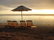 Sun loungers and parasols on a sandy beach. At sunset Royalty Free Stock Photography