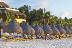Sun loungers and parasols on a tropical beach Royalty Free Stock Images