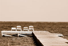 Sun loungers on pier. Sepia view of sun loungers on end of wooden pier with sea in background Stock Images