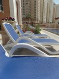 Sun loungers by the pool. On the Pearl island in Doha, Qatar royalty free stock images