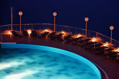 Sun loungers on poolside. Sun loungers on the poolside in a night scene Royalty Free Stock Photo
