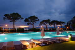 Sun loungers on poolside. At sunset with trees Stock Photos