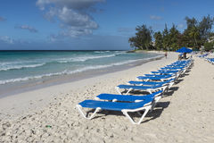 Sun loungers at Rockley Beach Barbados. Row of empty sun loungers lined up on Rockley Beach on the south coast of the Caribbean island of Barbados in the West royalty free stock photo