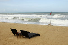 Sun loungers by rough sea. Sun loungers on sandy beach with red warning flag and rough ocean waves Stock Image