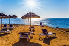 Sun loungers on sand beach. Holiday on an island in the Mediterranean Sea. Sun loungers on sand beach. The concept of luxury holiday seashore stock image
