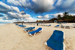 Sun loungers on sandy beach Royalty Free Stock Images