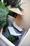 Sun loungers on small patio. Details of two sun loungers under straw parasol in small patio area, holiday apartment building stock photos