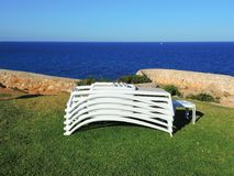 Sun loungers stacked with the background of the sea. Summer time royalty free stock photography