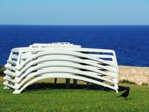 Sun loungers stacked with the background of the sea. Summer time stock photos
