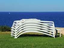 Sun loungers stacked with the background of the sea. Summer time royalty free stock photo