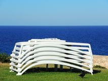 Sun loungers stacked with the background of the sea. Summer time stock images