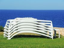 Sun loungers stacked with the background of the sea. Summer time royalty free stock images