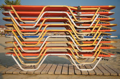Sun loungers stacked on beach. Close up of colorful sun loungers stacked on top of each other, beach scene royalty free stock photos