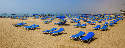 Sun loungers on sunny beach waiting for tourists sunbathing. Royalty Free Stock Images