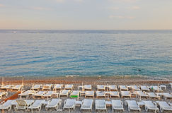 Sun loungers before sunset. Lot of sun loungers on the beach of Nice, France Royalty Free Stock Photography
