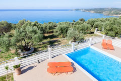 Sun loungers on terrace with swimming pool near sea. Orange sun loungers on terrace with swimming pool near blue sea in Greece royalty free stock image