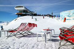 Sun loungers on top of snowy mountain in ski resort Stock Photo
