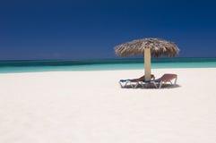 Sun loungers on tropical beach. Scenic view of two sun loungers under straw umbrella on tropical beach, summer scene stock photos