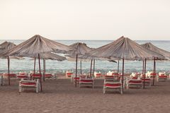 Sun loungers with an umbrella on the beach overlooking the sea. Summer concept royalty free stock photo