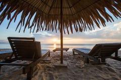 Sun loungers with umbrella on the beach, sunrise.  stock photography