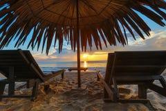 Sun loungers with umbrella on the beach, sunrise.  royalty free stock photo