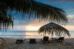 Sun loungers with umbrella on the beach, sunrise. Sun loungers with umbrella on the beach. sunrise stock photos