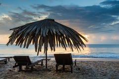 Sun loungers with umbrella on the beach, sunrise.  stock photo
