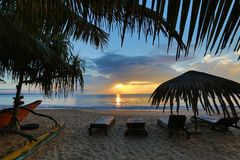 Sun loungers with umbrella on the beach, sunrise royalty free stock images