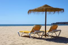 Sun Loungers and Umbrella on a Beach. Two sun loungers or deckchairs, and a parasol on a beautiful sandy beach with ocean view stock images