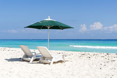 Sun loungers and umbrella on a tropical beach. Pair of sun loungers and umbrella on a tropical beach in Cancun, Mexico Stock Image