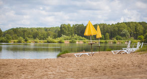 Sun loungers umbrellas on the coast. Deckchairs and yellow umbrellas on the shore of the lake Royalty Free Stock Photography