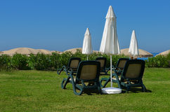 Sun loungers and umbrellas on the grass at the seaside. Sun loungers and white umbrellas are on green grass. Located on the seafront. you can see the sea and the stock photos