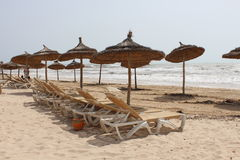 Sun loungers with umbrellas on the sea shore. On the sandy beach royalty free stock image