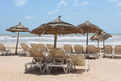 Sun loungers with umbrellas on the sea shore. On the sandy beach stock photo